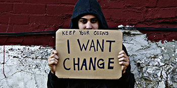 Homeless person holding sign 'Keep your coins, I want change'
